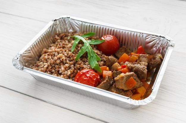 Comida saudável em caixa de papel alumínio com cereal de trigo sarraceno