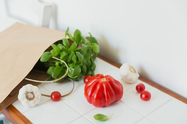 Comida saudável em um saco de papel de mantimentos na mesa branca com espaço de cópia