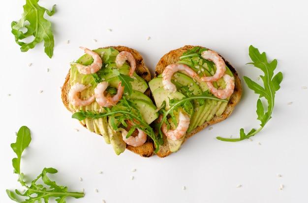 Comida saudável fitness. torradas com abacate, camarão e rúcula em forma de coração. nutrição apropriada. tiro aéreo.