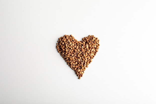 Comida saudável. forma de coração feita de grãos de trigo sarraceno em fundo branco. vista do topo. copie o espaço