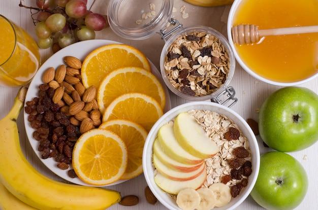 Comida saudável. frutas, granola caseira, nozes, aveia, mel, laranja