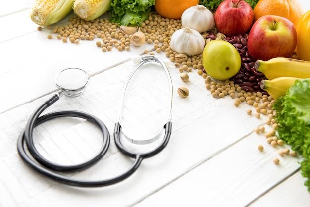 Comida saudável, frutas mistas e nozes, com estetoscópio na mesa de madeira