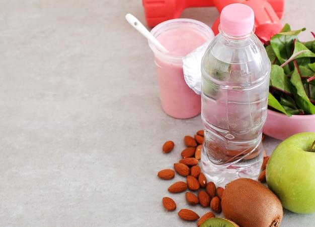 Comida saudável, halteres e garrafa de água