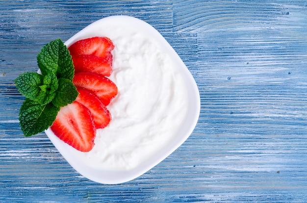 Comida saudável. iogurte branco natural com morangos frescos.