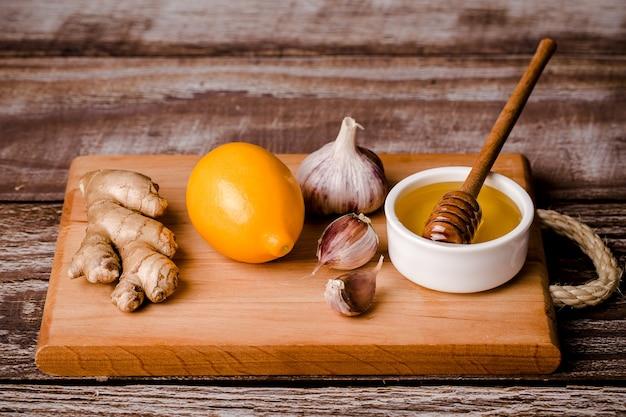 Comida saudável, kit de imunidade, vitamina c-mel, raiz de gengibre, limão, alho, em uma placa de madeira, fundo marrom