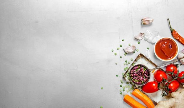 Comida saudável . legumes crus com feijão e especiarias. no fundo de aço