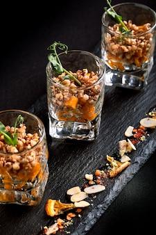 Comida saudável, muesli vegetariano vegetariano feito de trigo sarraceno verde e sementes de abóbora em um takan de vidro. fusion conceito de comida, chave baixa, copie o espaço.