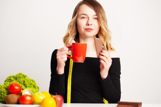 Comida saudável, mulher à mesa com legumes frescos e frutas comendo certo para perda de peso