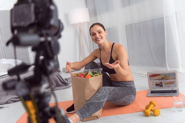 Comida saudável. mulher jovem e bonita e exuberante e atlética sorrindo e comendo um pacote de legumes enquanto está sentada no tapete e fazendo um vídeo para seu blog