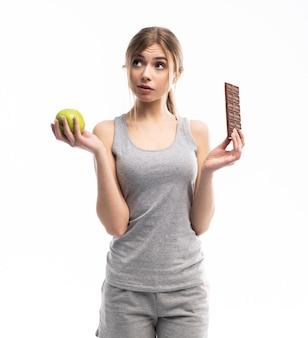 Comida saudável. mulher jovem e bonita escolhendo entre alimentos saudáveis e não saudáveis