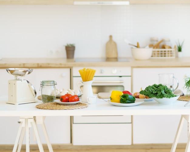 Comida saudável para cozinhar macarrão italiano e vegetais na mesa da cozinha em um apartamento moderno e iluminado
