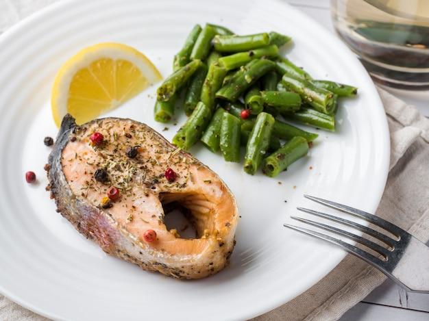 Comida saudável. peixe vermelho assado, salmão rosa, salmão e feijão verde com uma fatia de limão em um prato
