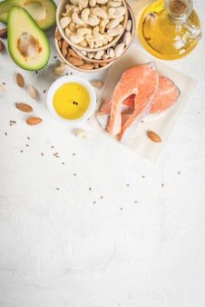 Comida saudável. produtos com gorduras saudáveis. omega 3, ômega 6. ingredientes e produtos: truta (salmão), óleo de linhaça, abacate, amêndoas, castanha de caju, pistache. em uma mesa de pedra branca. vista superior copyspace
