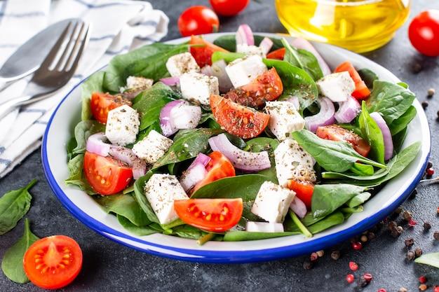 Comida saudável. salada grega com espinafre, tomate, pimentão, cebola roxa, queijo feta em um fundo escuro de concreto