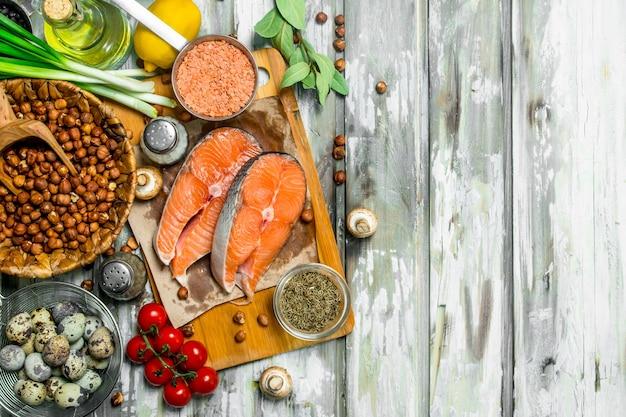 Comida saudável. salmão com vegetais orgânicos, frutas e nozes. sobre um fundo rústico.