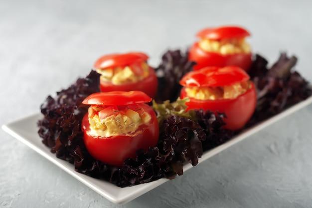 Comida saudável. tomate recheado com legumes com alface.