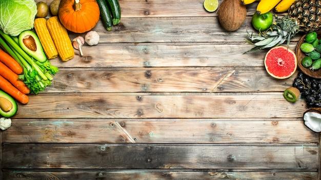 Comida saudável. variedade de frutas e vegetais orgânicos frescos na mesa de madeira.