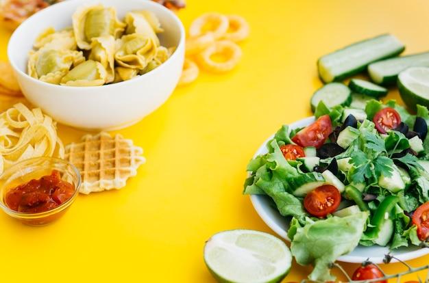 Comida saudável vs alimentos pouco saudáveis na mesa amarela