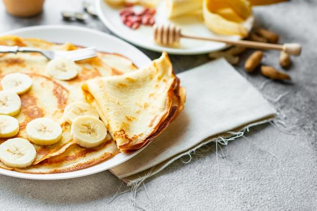Comida, sobremesa, pastelaria, panqueca, torta. saborosas panquecas bonitas com banana e mel em um fundo de concreto