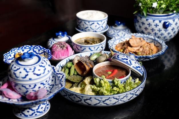 Comida tailandesa, arroz, peixe e pasta de pimenta na mesa