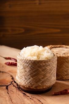 Comida tailandesa asiática arroz glutinoso ou pegajoso em vime de bambu em fundo de madeira com espaço de cópia
