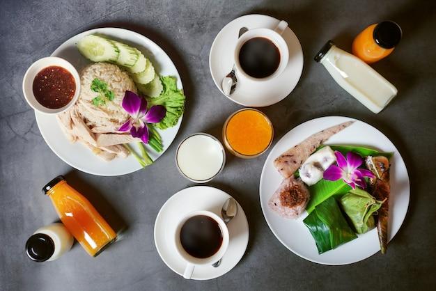 Comida tailandesa café da manhã, leite, suco de laranja, xícara de café e vegetais