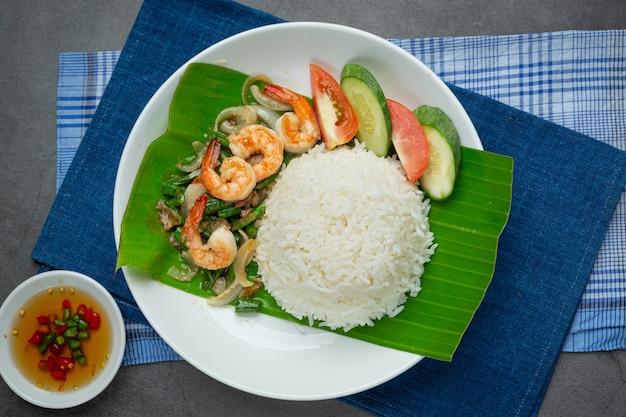 Comida tailandesa; camarão e lula fritos cozidos com feijão comprido e arroz.