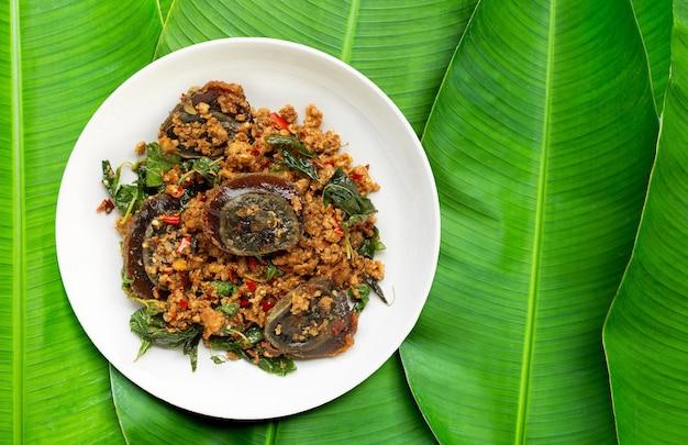 Comida tailandesa. carne de porco frita e picada, ovo em conserva com folhas de manjericão em folhas de bananeira.