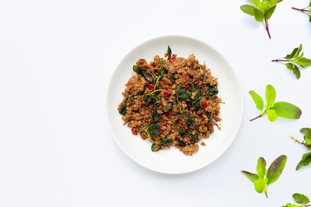 Comida tailandesa. carne de porco picada frita com folhas de manjericão no fundo branco.