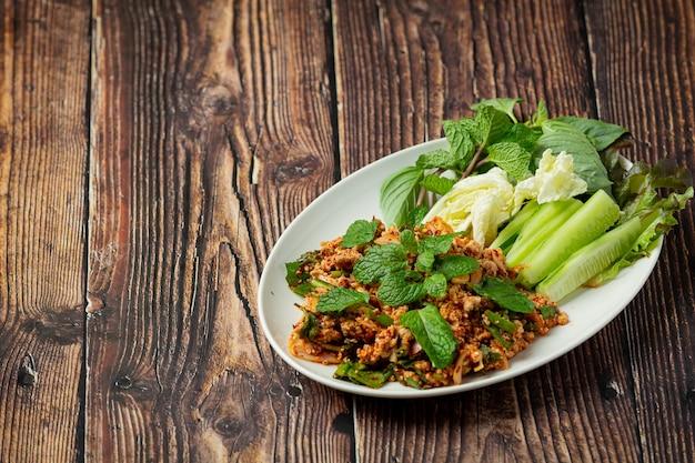 Comida tailandesa; carne picada de porco picante servida com acompanhamentos