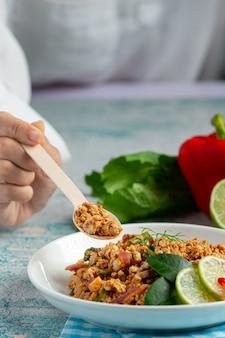 Comida tailandesa com carne de porco picada picante e acompanhamentos