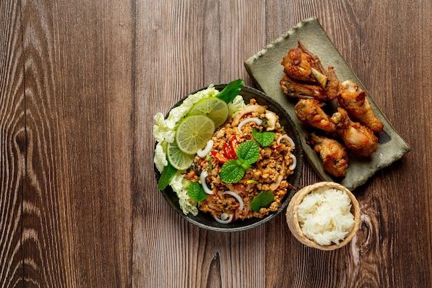 Comida tailandesa com carne de porco picada picante servida com arroz pegajoso e frango frito