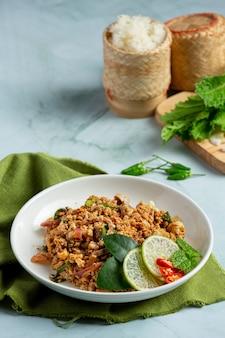 Comida tailandesa com carne de porco picante picada servida com acompanhamentos e arroz pegajoso