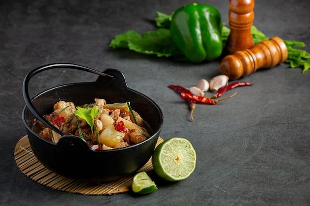 Comida tailandesa com sopa picante de perna de porco em tigela preta