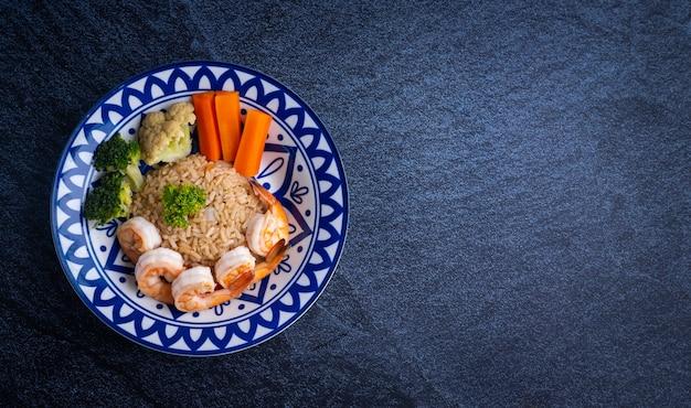 Comida tailandesa composta por arroz, camarão fresco, legumes e pasta de pimentão