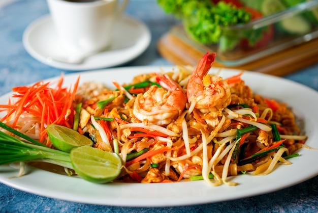 Comida tailandesa de macarrão, almofada tailandês sobre fundo azul com cebola e limão ao lado da placa