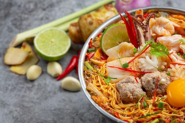 Comida tailandesa. macarrão picante ferva com frutos do mar e carne de porco na panela quente