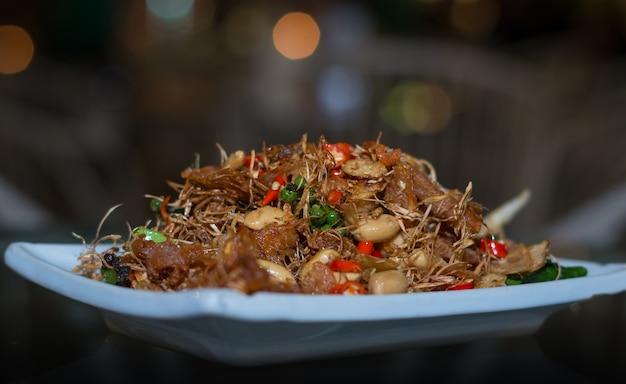 Comida tailandesa, peixe frito mexido com castanha de caju no sabor das especiarias