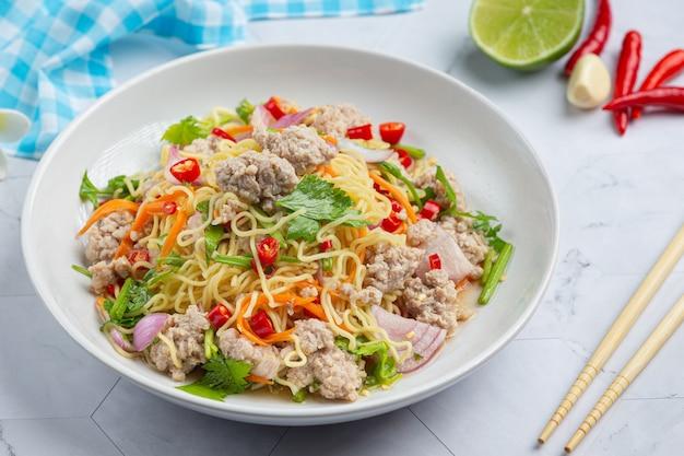 Comida tailandesa. salada picante de macarrão instantâneo com carne de porco picada