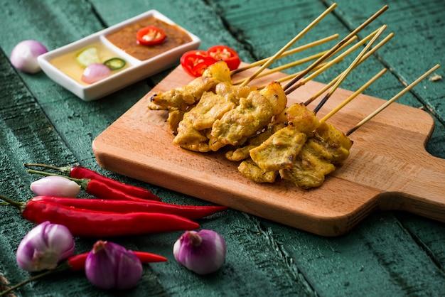 Comida tailandesa, satay de porco grelhado com molho de amendoim e vinagre