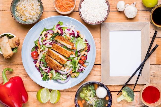 Comida tailandesa tradicional com moldura em branco e pauzinhos na mesa de madeira