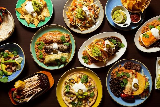 Comida típica mexicana, tacos, tamales, guacamole, tostadas, fajitas, vista superior em fundo de madeira