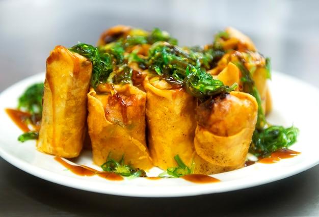 Comida tradicional chinesa de rolinhos primavera, prato de servir e salada de algas, foco seletivo