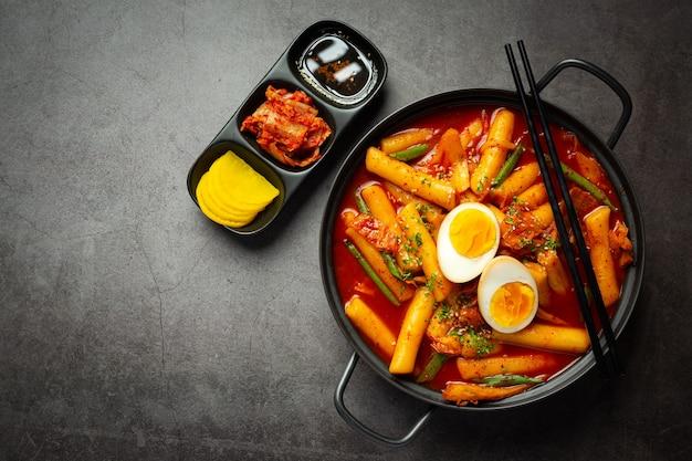 Comida tradicional coreana de queijo tokbokki no fundo do quadro negro. prato de almoço.