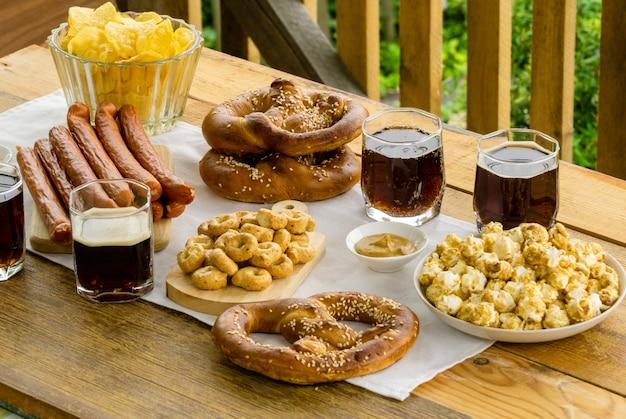 Comida tradicional de festa de outubro. salsicha, lanches e cerveja em uma mesa de madeira