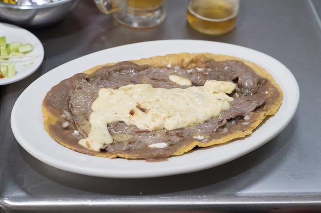 Comida tradicional mexicana de huarache com carne e queijo.