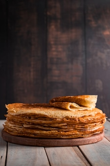 Comida tradicional russa - panquecas finas. uma pilha de crepes em um fundo de madeira marrom escuro. estilo rústico.
