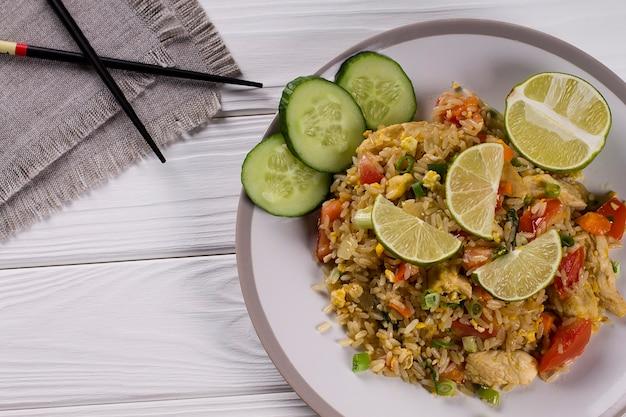 Comida tradicional tailandesa. arroz frito com legumes, especiarias e limão. khao pad