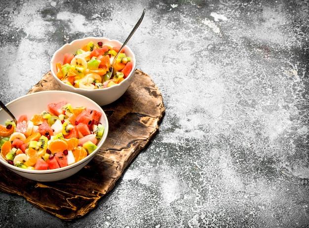Comida tropical. salada de frutas tropicais. sobre fundo rústico.