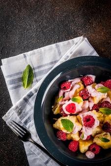 Comida ucraniana, russa, vareniki preguiçoso; nhoque de requeijão ou queijo com framboesas cruas frescas, creme e hortelã